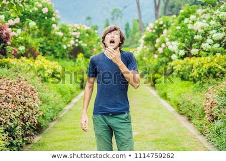 Fiatalember tüsszentés park virágzó fa allergia Stock fotó © galitskaya