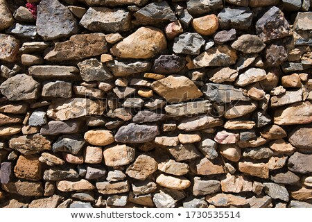Texture of an old stone wall from uneven different ancient stone Stock photo © boggy