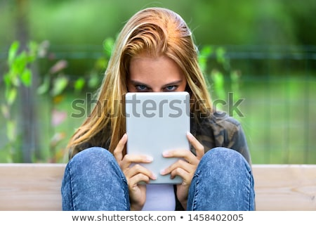 Mysterious young woman peering over a tablet-pc Stock photo © Giulio_Fornasar