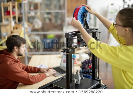 Young female office worker changing spool with red filament on 3d printer Stock photo © pressmaster