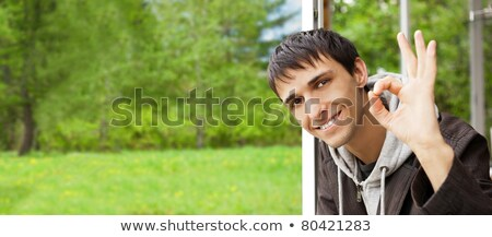 young brunette man gives the ok sign standing near big window a stock photo © hasloo