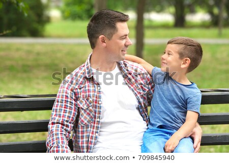 Father and son sitting on a bench together on a sunny day Stock photo © photography33