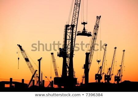 Silhouette of several cranes in a harbor, shot during sunset. Stock photo © cozyta