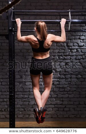 Back view of young bodybuilder at horizontal bar Stock photo © julenochek