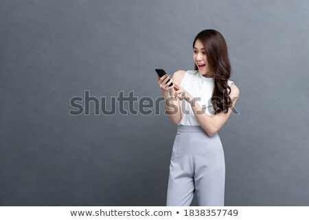 surprised pretty businesswoman chatting by phone stock photo © deandrobot