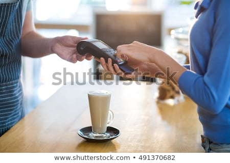 Waiter holding cup of coffee in café Stock photo © wavebreak_media