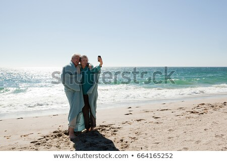 Couple at the beach in blanket, photographing themselves Stock photo © IS2