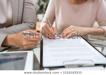 One of two businesswomen with pens going to put signature on page of contract Stock photo © pressmaster