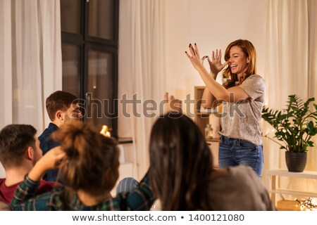 friends playing guessing game at home in evening Stock photo © dolgachov