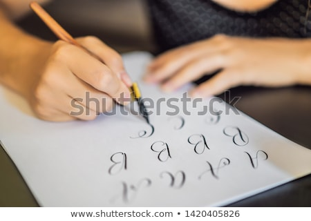 Lettering, calligraphy, writes phrase on white paper. Inscribing ornamental decorated letters. Calli Stock photo © galitskaya
