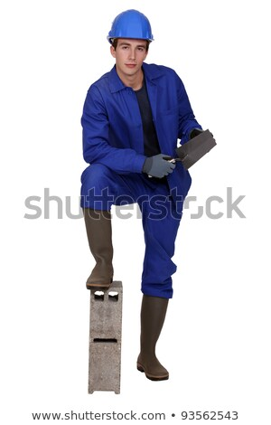 young bricklayer with leg resting on block of concrete holding trowel Stock photo © photography33