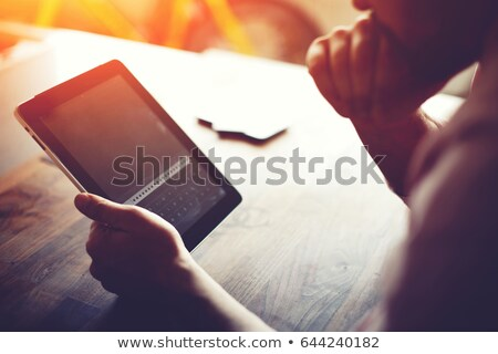 young business man holds tablet and looking up pensively Stock photo © feedough