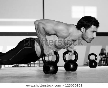 Kettlebells push-up man strength gym workout Stock photo © lunamarina