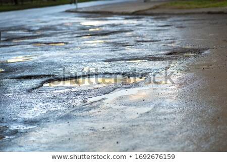 damaged car of road full of cracked potholes in pavement Stock photo © vladacanon