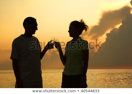Man and woman clink glasses. Silhouettes against sea. Stock photo © Paha_L
