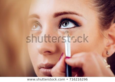 makeup artist applying concealer Stock photo © LightFieldStudios