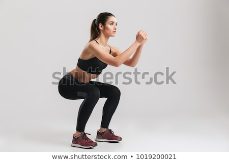 Portrait of beautiful sportswoman in tracksuit doing sit-ups, wh Stock photo © deandrobot