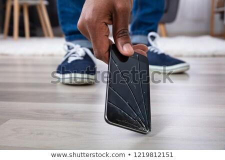 Man Picking Up Damaged Mobile Phone Stock photo © AndreyPopov