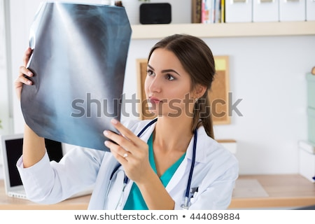 Young female doctor or intern looking at  x ray image at her off Stock photo © boggy