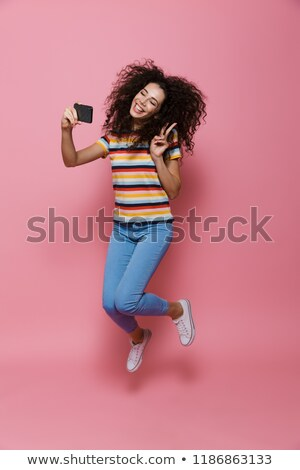 Photo of amusing woman 20s with curly hair smiling and holding g Stock photo © deandrobot