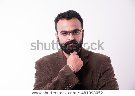 Serious young bearded man in formalwear and eyeglasses looking through notes Stock photo © pressmaster