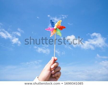 close up of hand holding pinwheel toy over sky Stock photo © dolgachov