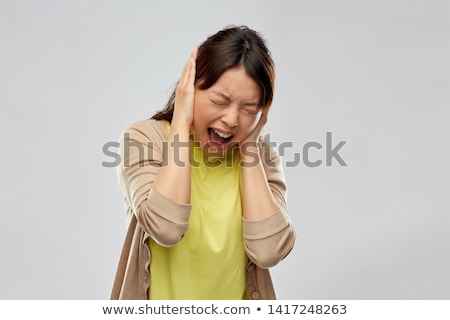 stressed asian woman closing ears and screaming Stock photo © dolgachov