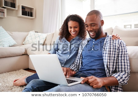 Young couple sitting on a sofa with a laptop Stock photo © photography33