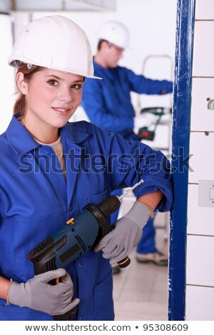 Stock photo: Young female electrician with a power drill
