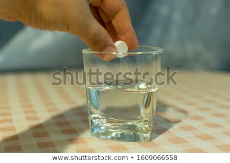 Tablet of sedative in a hand above a glass with water Stock photo © ozaiachin