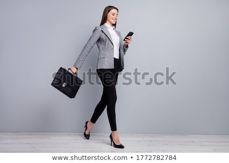 Profile of a businesswoman smiling with a suitcase and holding a coffee against white background stock photo © wavebreak_media