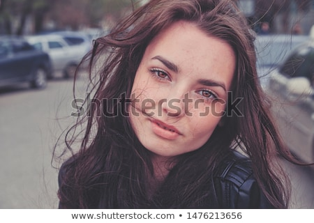 Portrait of cute young woman looking at camera in the street. Stock photo © deandrobot