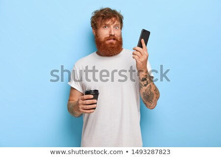 Redhair man with mobile phone by wall Stock photo © boggy