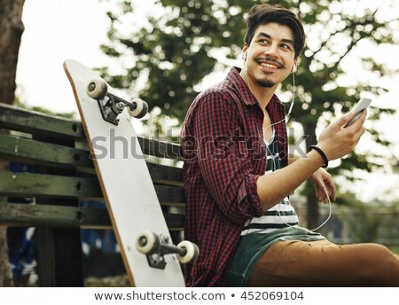 smiling young man with skateboard and smartphone Stock photo © dolgachov