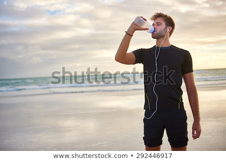 Young sports man standing on the beach drinking water listening music. Stock photo © deandrobot