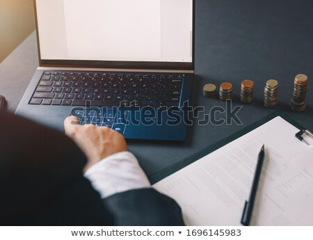 Businessperson Calculating Stacked Coins Stock photo © AndreyPopov