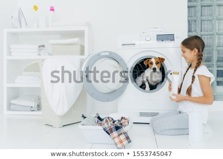 Cheerful little girl stands on knees with washing detergent, poses near washing machine, looks happi Stock photo © vkstudio