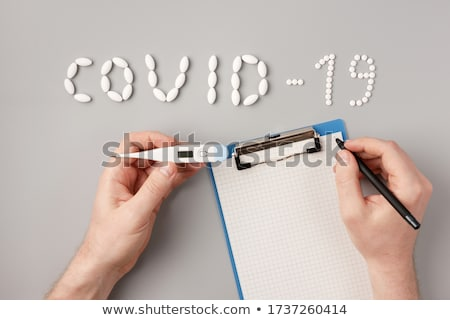 The inscription Covid-19 of tablets, tablets and a thermometer on a red background. Stock photo © Illia
