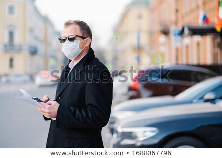 Pandemic coronavirus outbreak. Serious businessman poses outdoor near transport at street, holds mod Stock photo © vkstudio