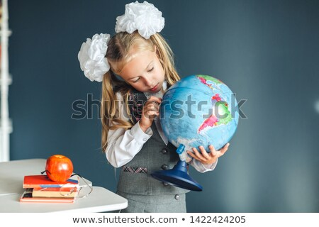Stock photo: Young schoolgirl pointing to a destination on a globe