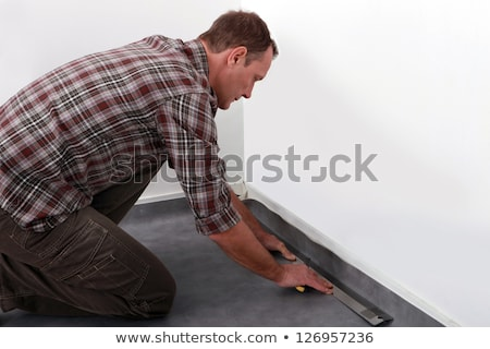 Tradesman laying down linoleum flooring Stock photo © photography33