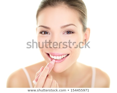 pretty young woman applying lip gloss on white background stock photo © lightpoet