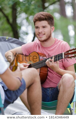 Teenager with guitar sat with friends Stock photo © photography33