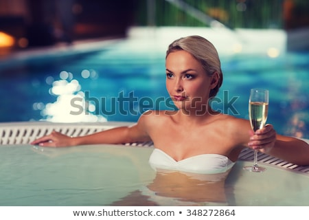 happy woman sitting in jacuzzi at poolside Stock photo © dolgachov