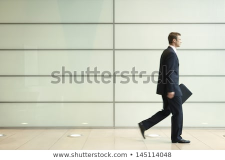 Side view of young businessman walking in passage of office Stock photo © HASLOO