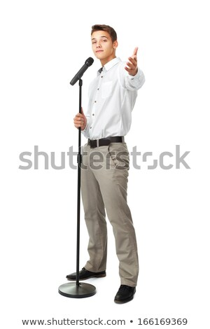Stock photo: Attractive young man singer holding microphone and pointing on you
