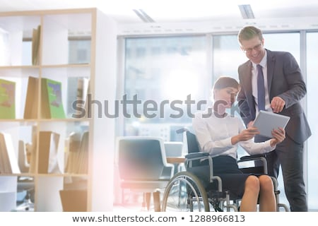 Stock photo: Businessman discussing with colleague over digital tablet