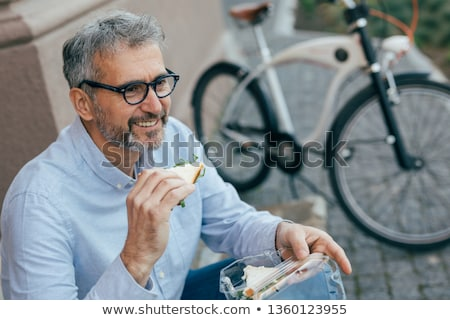 Man with bicycle having lunch break Stock photo © IS2