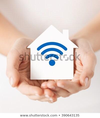 hands holding house with radio wave signal icon stock photo © dolgachov