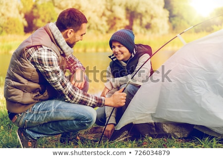 happy parents and son setting up tent at campsite Stock photo © dolgachov